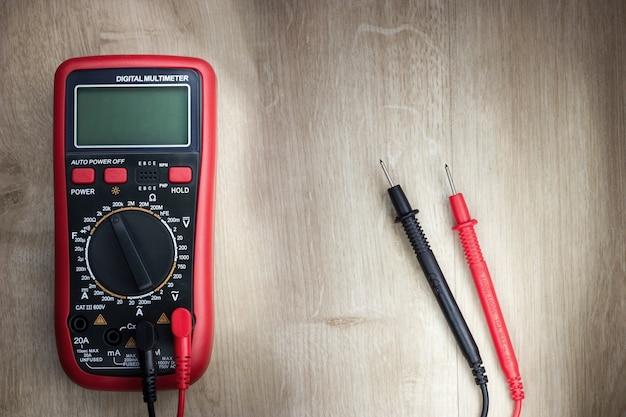 木製の背景にデジタル電気テスターマルチメーター。クローズアップ写真。