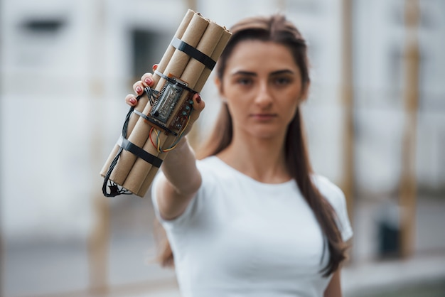 디지털 요소. 시한 폭탄을 보여줍니다. 위험한 폭발성 무기를 손에 들고 젊은 여자