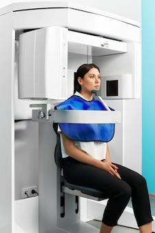 防護服を着た患者の女性との歯科検診用のデジタル機器。