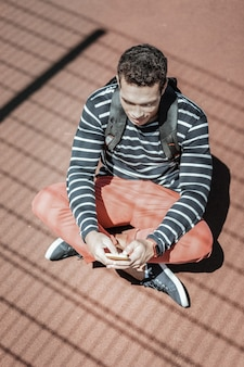 Digital era. top view of appealing young guy using phone and having seat on ground