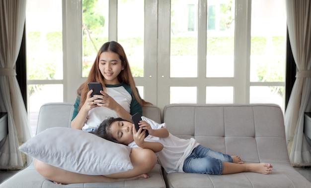 Концепция мобильного телефона наркомана цифрового поколения с азиатской девушкой и сестрой дома