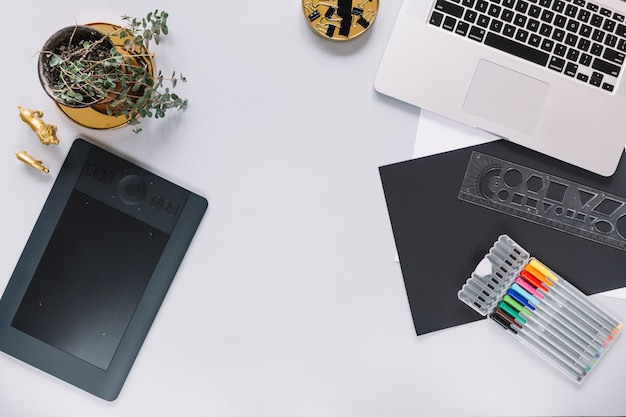 La tavoletta grafica ed il computer portatile di digital deridono su con gli oggetti dell'ufficio su fondo bianco