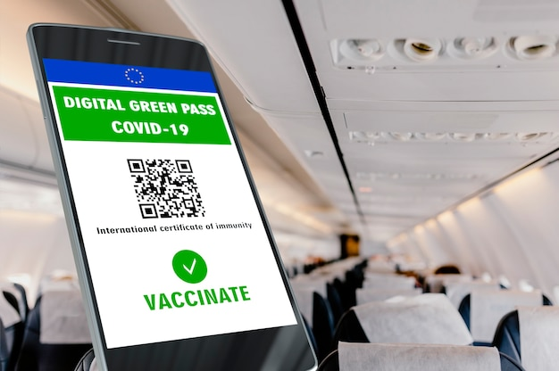 Digital green pass of the european union with the qr code on a mobile screen, interior background of an airplane. covid-19 immunity. travel without restrictions.