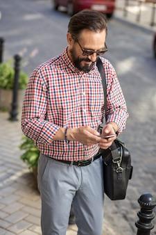 デジタルライフスタイル。メッセージを入力しながら通りに立っている楽しい喜びの男