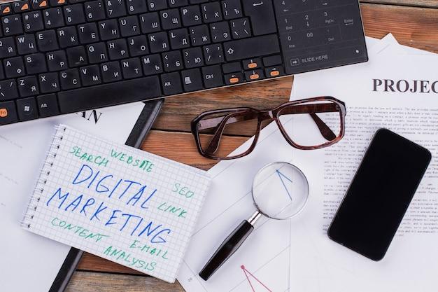 メモ帳のデジタルマーケティングと茶色の背景のさまざまなビジネスペーパー