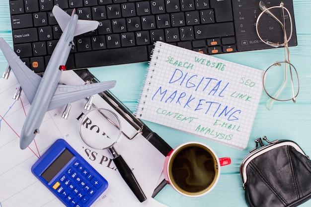 メモ帳やさまざまな事務用品のデジタルマーケティング。青い背景にキーボード、コーヒー、その他のオフィス関連のオブジェクトを使用したフラットレイコンポジション。