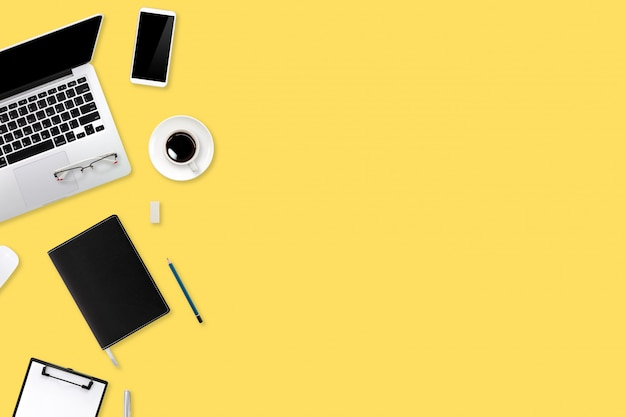 Digital marketing work desk with laptop computer, office supplies, coffee cup and cell phone on yellow pastel