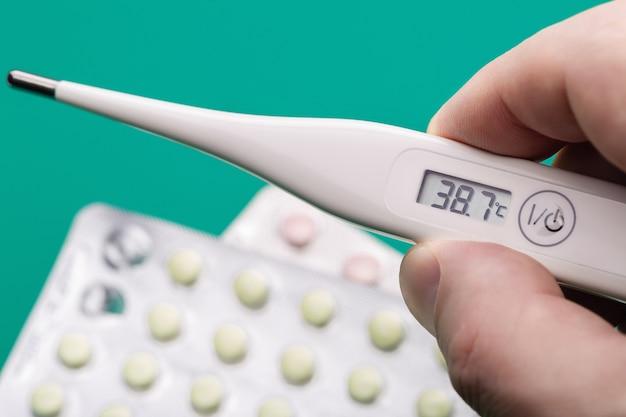 人間の手で測定値を持つデジタル体温計。痛みを和らげるピル。閉じる。ヘルスケアの概念。