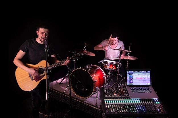音楽を録音するコンピューターを備えたレコーディングスタジオのデジタルミキサー。背景には、ミュージシャンが楽器を演奏します。創造性とショービジネスのコンセプト。