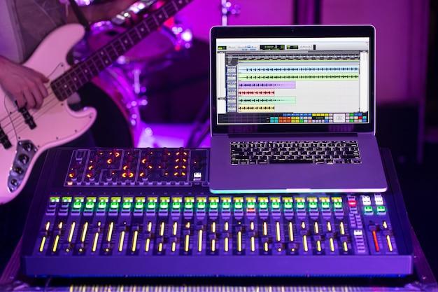 音楽を録音するコンピューターを備えたレコーディングスタジオのデジタルミキサー。ベースギターを持つ男の背景に。創造性とショービジネスのコンセプト。
