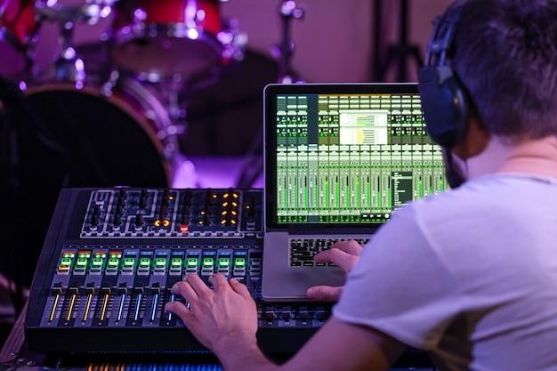 音楽を録音するコンピューターを備えたレコーディングスタジオのデジタルミキサー。職場のサウンドエンジニアの背景について。創造性とショービジネスのコンセプト。