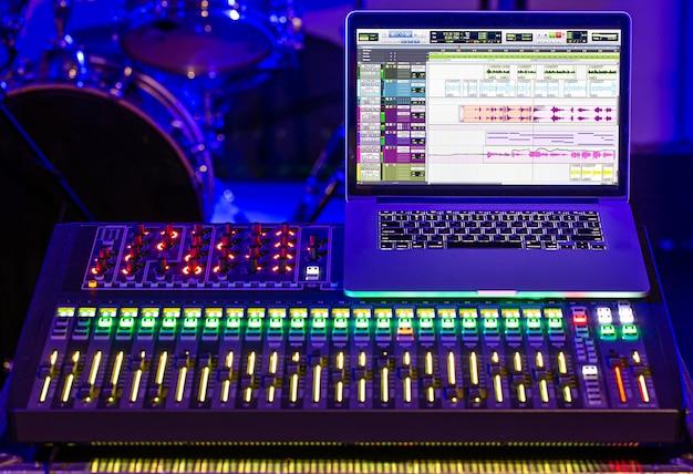 サウンドと音楽を録音するためのコンピューターを備えたレコーディングスタジオのデジタルミキサー。創造性とショービジネスの概念。