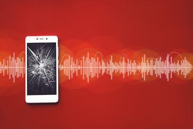 오디오 트랙이 있는 빨간색 배경에 깨진 검은색 화면이 있는 디지털 휴대 전화.