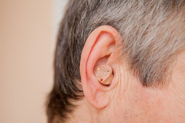 Digital modern hearing aid in the ear of an old man