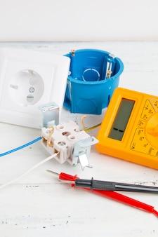 Цифровой мультиметр, электрическая розетка и выключатель