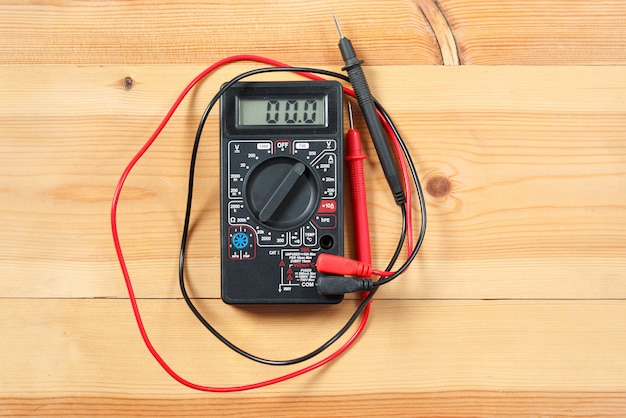 Digital multimeter and wiring on wooden table