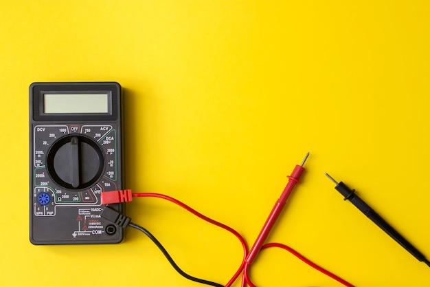 黄色の背面にプローブとバックライト付きディスプレイを備えたデジタルマルチメータ。マルチメータまたはマルチテスター