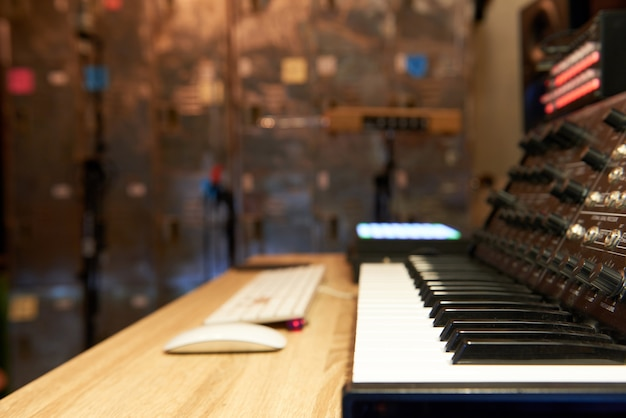 Digital music composer with keyboard and mixer in home studio with soft shutter