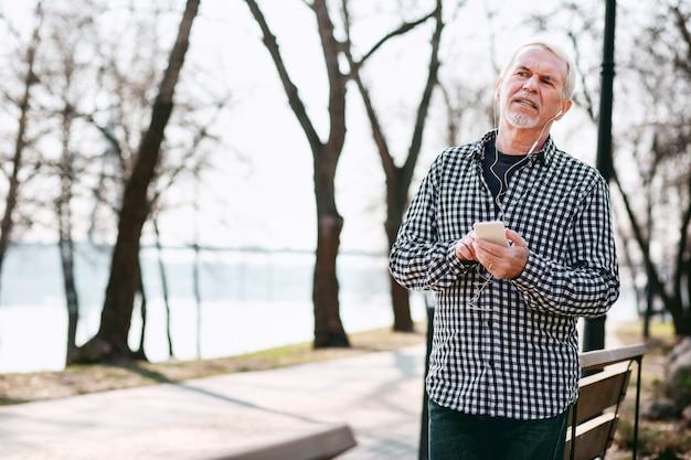 Цифровая музыка. доволен старший мужчина, опираясь на скамейку и слушающий музыку