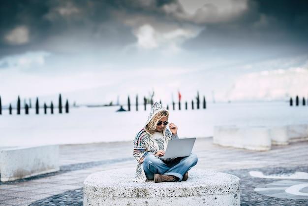 大人の若い女性と一緒にどこでもデジタル遊牧民とテクノロジーの仕事の概念は、空の下の代替の無料のオフィスでラップトップコンピューターとインターネットローミング接続を使用して屋外で座っています