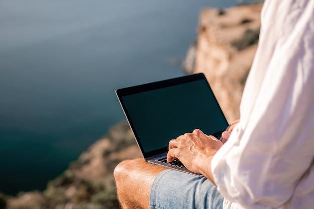 帽子をかぶったデジタル遊牧民の男ノートパソコンを持っているビジネスマンは日没時に海のそばの岩の上に座っています