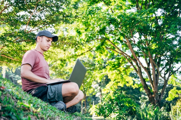 Digital nomad man working in the forest