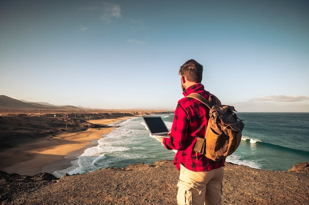 立っている人とのデジタル遊牧民のスマートな作業の概念は、ラップトップコンピューターと素晴らしいビーチの景色を望む野生の屋外の場所でローミングするインターネット接続で動作します
