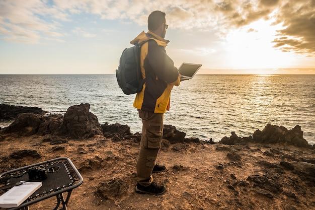 Digital nomad traveler man at work lokking an amazing golden sunset on the ocean