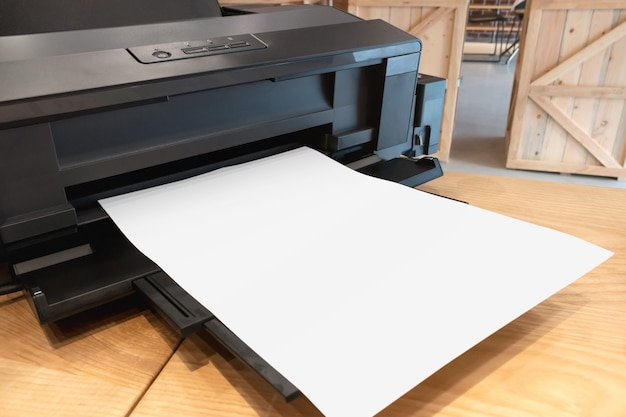 Digital paper printer and blank template on wooden table.