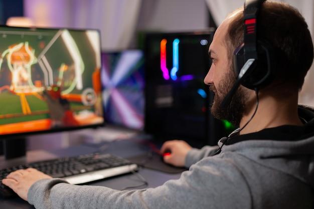 Цифровой игрок в наушниках играет в видеоигры с современной графикой для чемпионата по шутерам. онлайн-трансляция кибер-выступления во время игрового турнира с использованием мощного пк с rgb-подсветкой