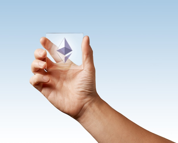 On the digital screen icon of ethereum man is holding in his hand on a blue surface. conceptual image for crypto currency market, technology and cryptocurrency