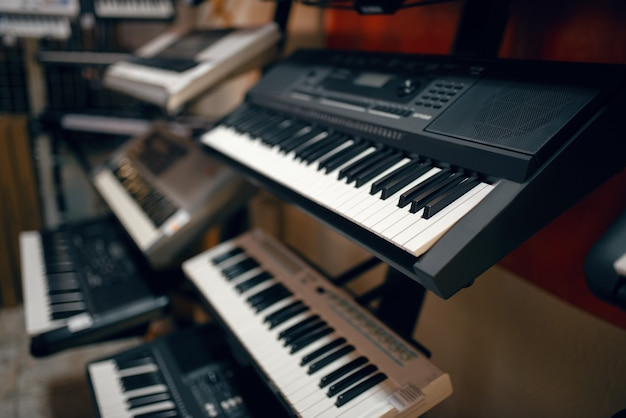Digital synthesizers on showcase in music store, closeup view.