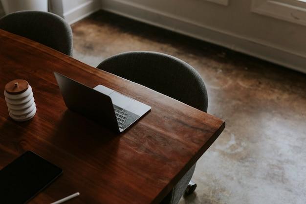 会議室の木製テーブルにデジタルタブレットとラップトップ