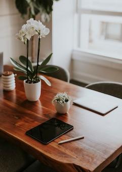 デジタルタブレットとノートパソコンをオフィスの木製テーブルに