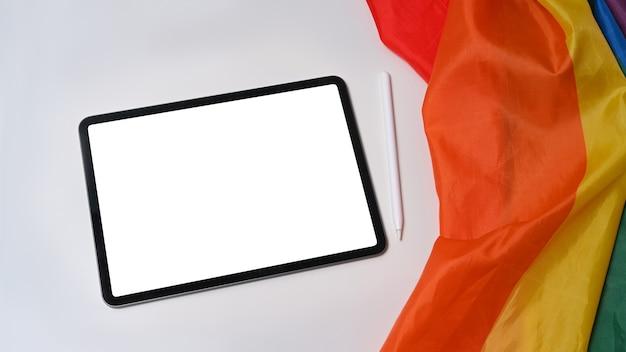 Цифровой планшет и флаг гордости лгбт на белом фоне.
