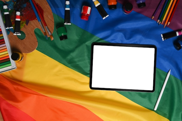 Digital tablet and artist tools over colorful rainbow flag.