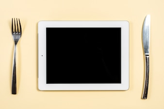 Digital tablet between the fork and butterknife on beige background