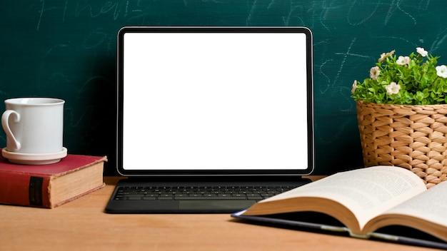 녹색 칠판 위의 나무 테이블에 빈티지 홈 학교 장식 용품이 있는 디지털 태블릿 빈 화면 모형