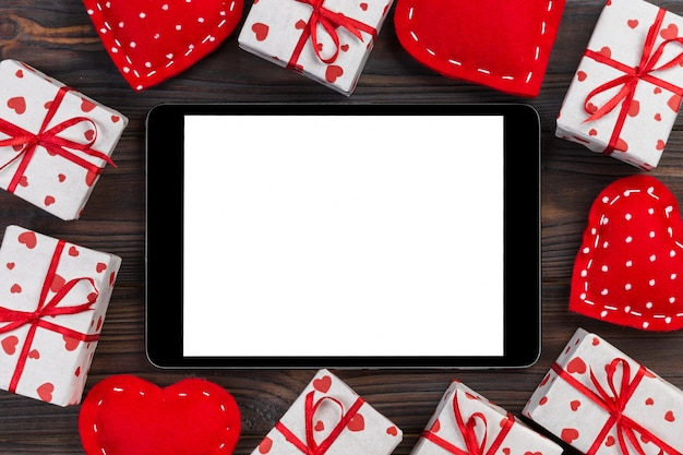 Digital tablet blank screen with gift box and hearts decor on wooden table. top view.