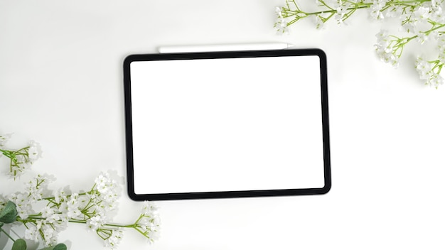 Digital tablet on centre frame with flower bouquet, empty screen display for present.