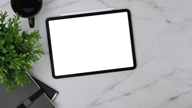 Цифровой планшет, кофейная чашка, комнатное растение и ноутбук на мраморном столе.