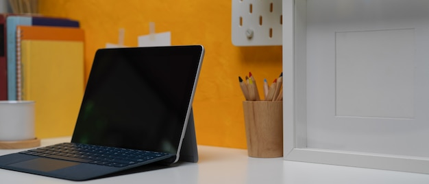 Digital tablet on creative home office desk with stationery,  frame and books