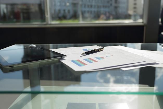 커피 테이블에 디지털 태블릿 금융 차트와 펜