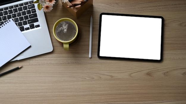 Цифровой планшет, ноутбук и кофейная чашка на деревянном столе.