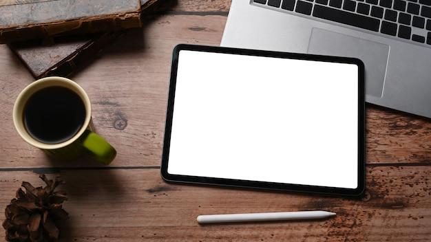 Цифровой планшет, портативный компьютер, кофейная чашка и шишка на деревянном столе.