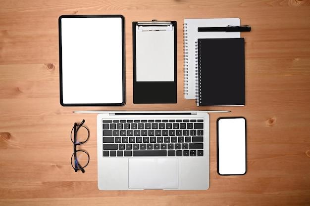 木製の背景にデジタルタブレット、ラップトップ、スマートフォン、メモ帳。