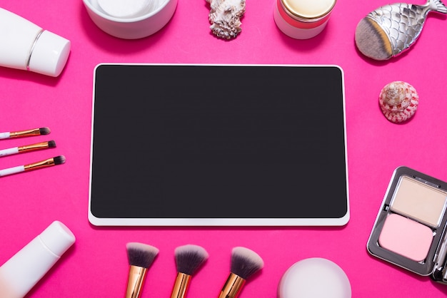 Digital tablet and lot of make up on pink table, top view, flatlay