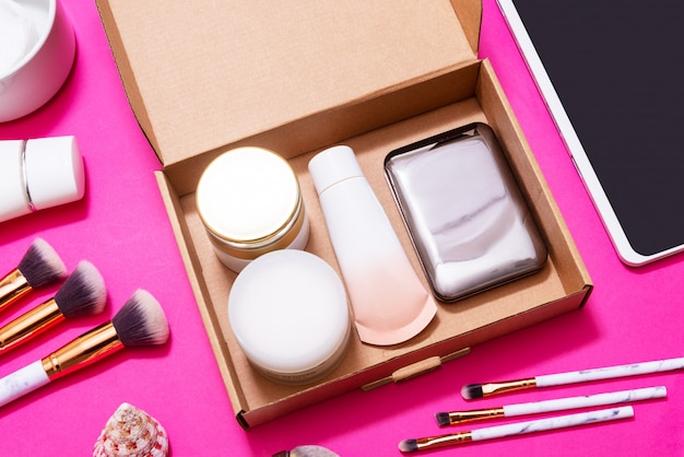 Digital tablet and makeup subscription boxes on pink table, top view, flatlay