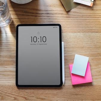 木製のテーブルの上のデジタルタブレットのモックアップ