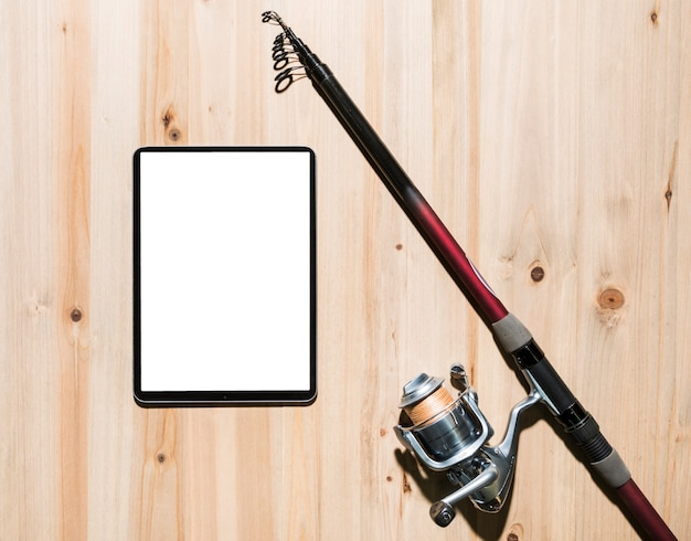 Digital tablet near the fishing rod on wooden desk